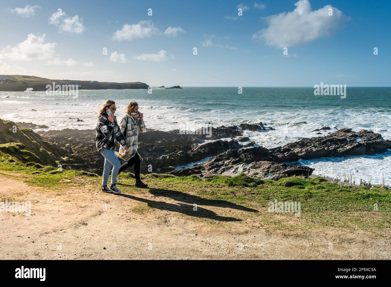 Zwei Freundinnen, die auf dem Küstenpfad auf der Landzunge in Newquay in Cornwall spazieren. Stockfoto