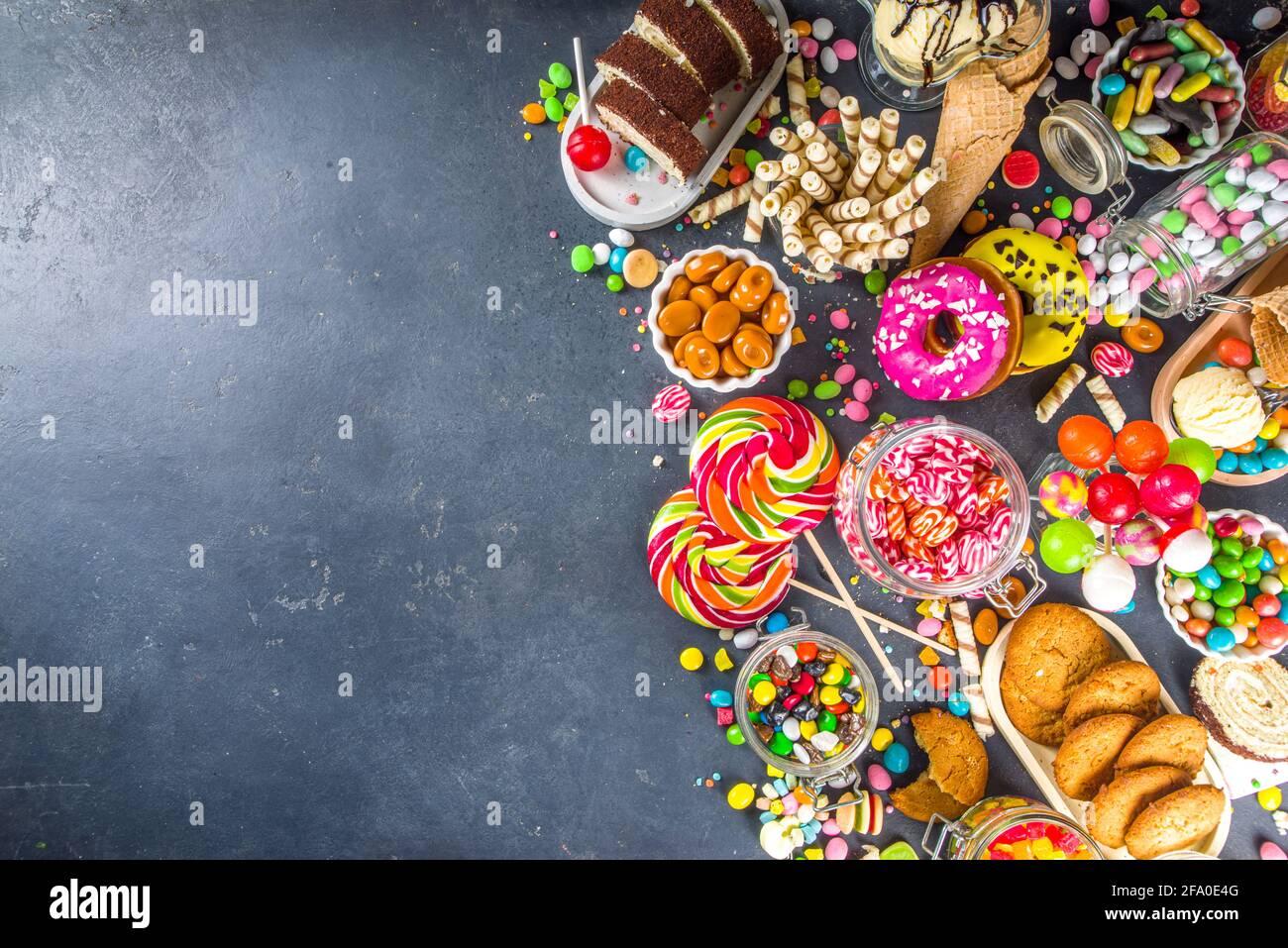 Auswahl an bunten Süßigkeiten. Set mit verschiedenen Süßigkeiten, Pralinen, Donuts, Keksen, Lutschern, Eiscreme von oben auf schwarzem Betonhintergrund Stockfoto