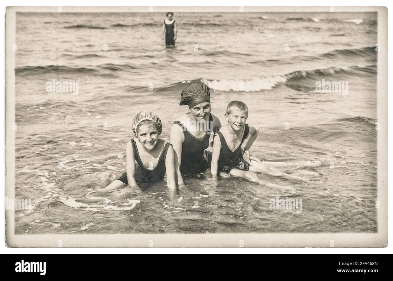 Alte Foto Mutter und Kinder auf dem Meer. Sommerurlaub. Vintage-Bild mit Original-Film-Körnung und Unschärfe aus ca. 1920 Stockfoto