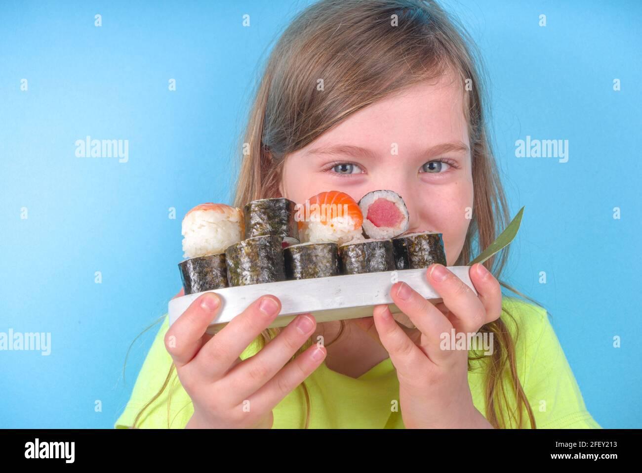 Nettes kleines Mädchen genießt Sushi zu essen. Fröhliche lustige kaukasische blonde Vorschule Kindermädchen mit verschiedenen Sushi-Rolle und Essstäbchen. Auf hellblauem Hintergrund Stockfoto