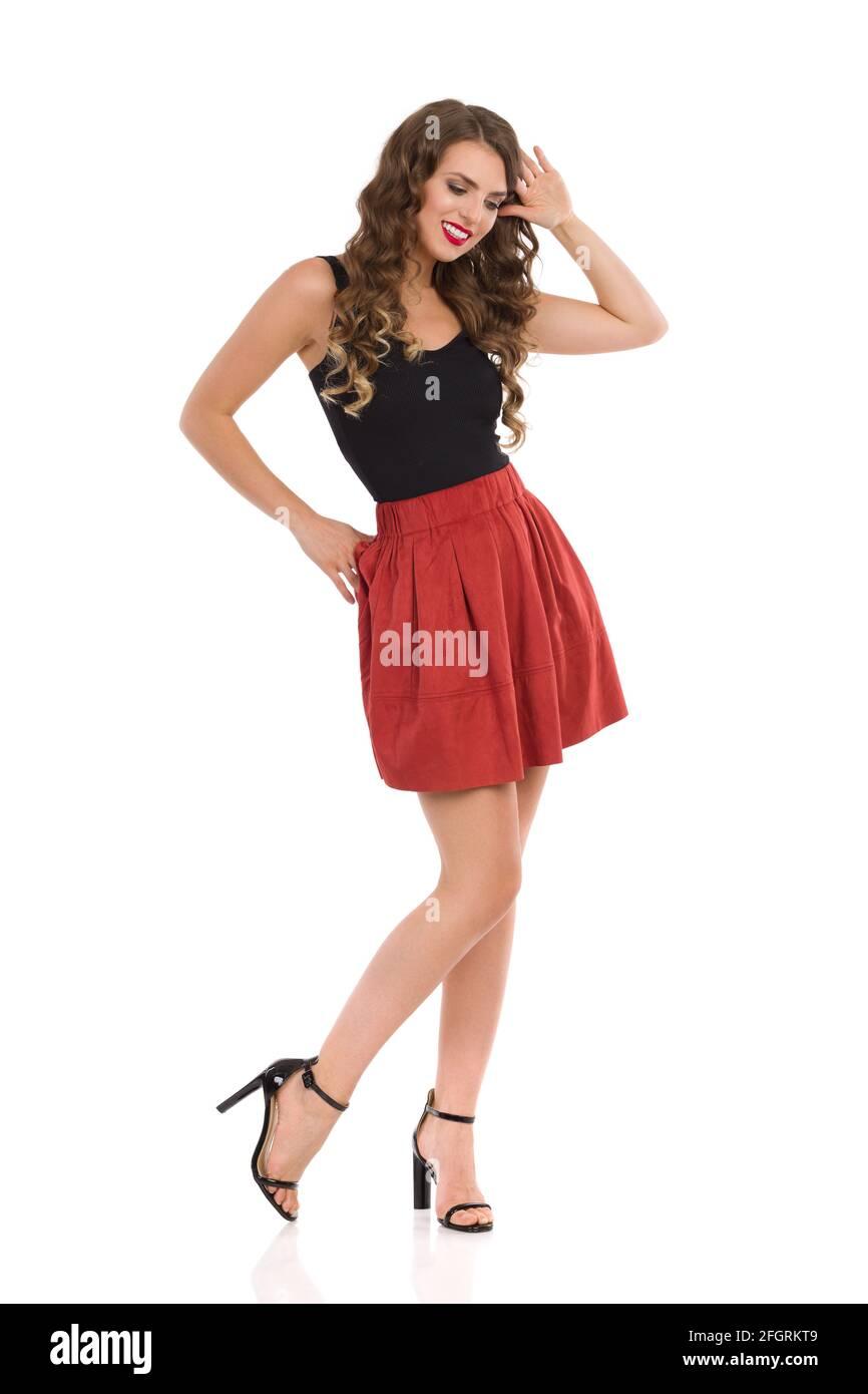 Glückliche junge Frau posiert in braunem Minirock aus Wildleder, schwarzem Oberteil und High Heels. Studioaufnahme in voller Länge, isoliert auf Weiß. Stockfoto