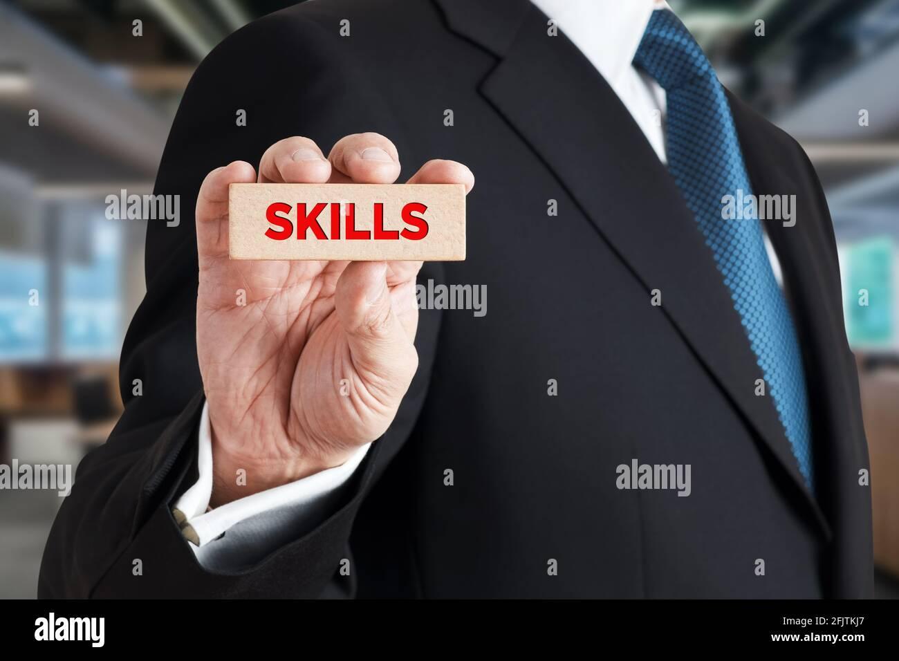 Geschäftsmann zeigt einen Holzblock mit dem Wort Fähigkeiten. Business- oder Berufsqualifikation, Kompetenz- oder Führungskräftekonzept. Stockfoto