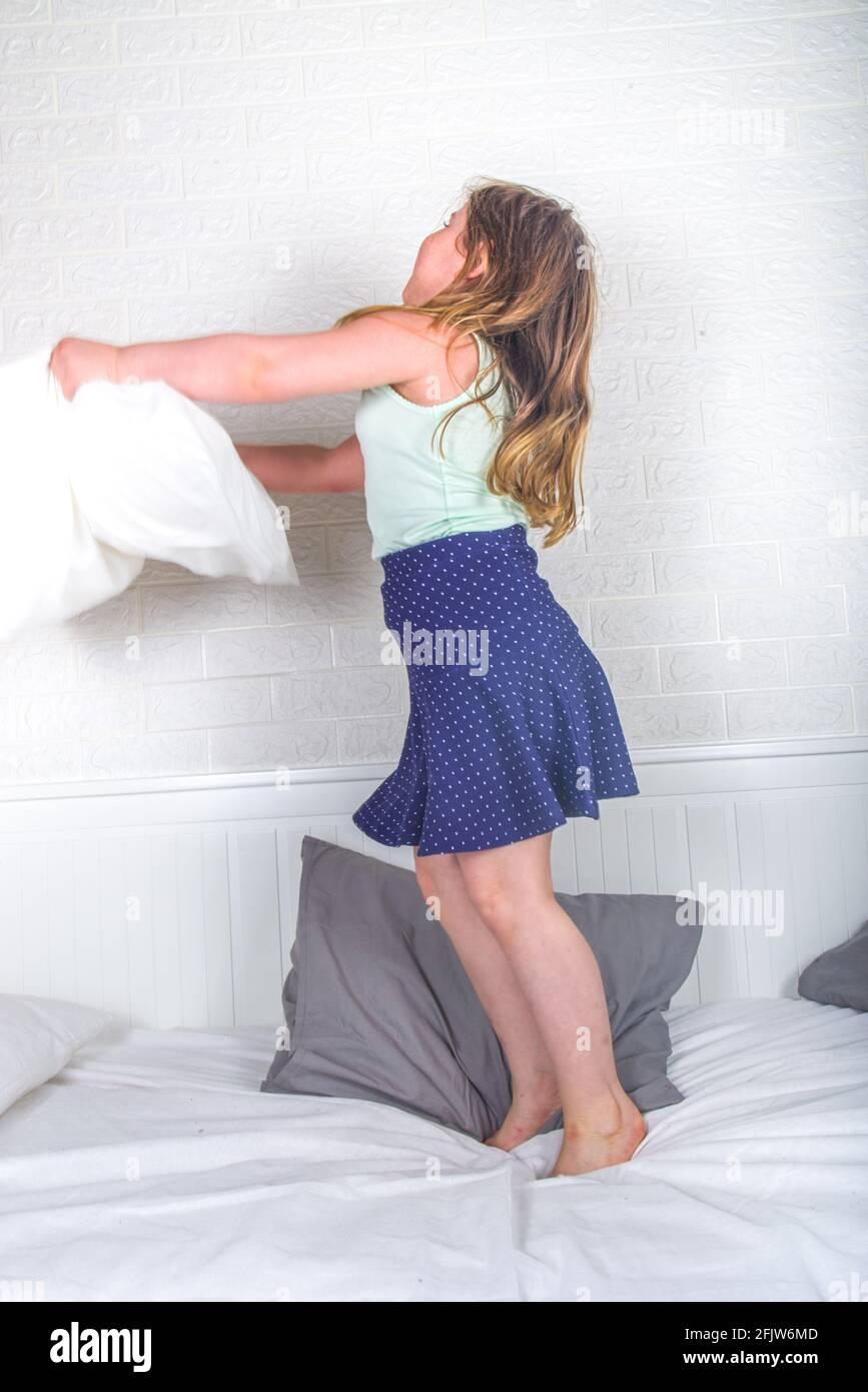 Kleine niedliche Kleinkind Vorschulmädchen springen auf Sofa werfen Kissen, Hause Freizeit Freizeit Hintergrund, Lockdown Konzept Stockfoto