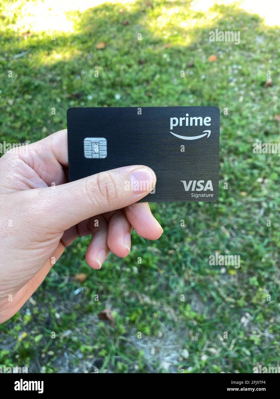 Eine Frau hält eine Amazon Prime Rewards Visa Signature Card in