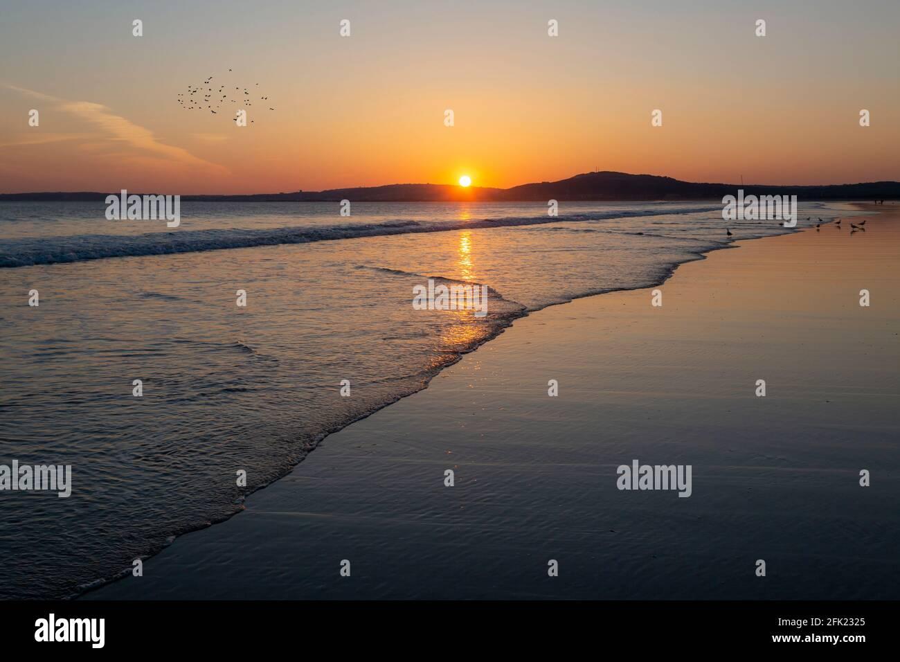 Sonnenuntergang über dem riesigen Sandstrand von Aberavon in Port Talbot, South Wales, Großbritannien Stockfoto