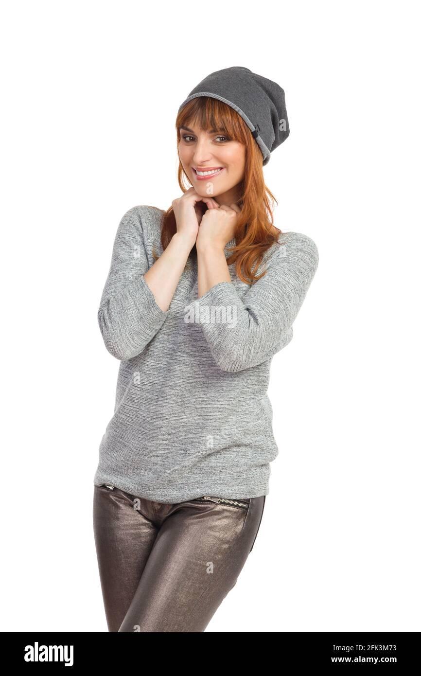 Portrait einer niedlichen Frau in grauer Bluse, glänzender Hose und Wintermütze. Vorderansicht. Drei Viertel lange Studioaufnahmen isoliert auf Weiß. Stockfoto