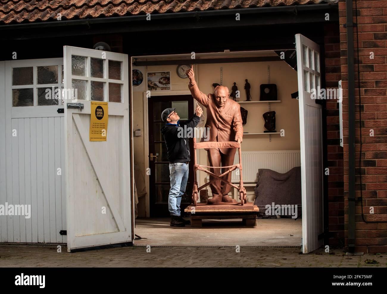 Andrian Melka verleiht seiner zwei Meter hohen Tonstatue von Captain Sir Tom Moore in seinem Atelier in der Nähe von York den letzten Schliff. Der Bildhauer ist Crowdfunding, um die Arbeit in Bronze gießen zu lassen, damit er sie dem Leeds Teaching Hospitals NHS Trust spenden kann. Bilddatum: Mittwoch, 28. April 2021. Stockfoto