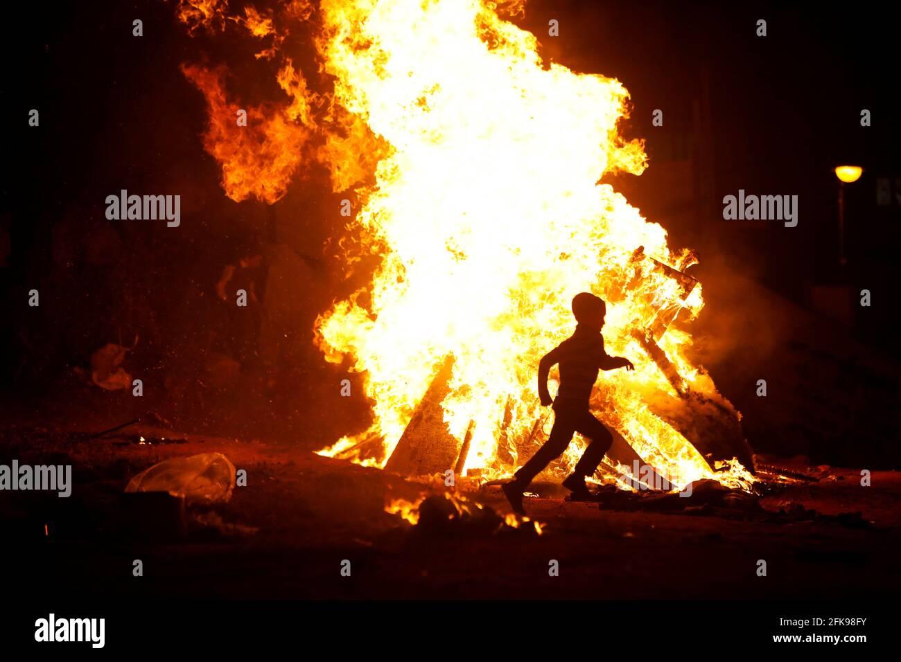 Ein Junge rennt um ein Lagerfeuer, als Ultra-orthodoxe Juden den jüdischen Feiertag von lag Ba'Omer in Bnei Brak, nahe Tel Aviv, Israel, am 29. April 2021, markieren. REUTERS/NIR Elias Stockfoto