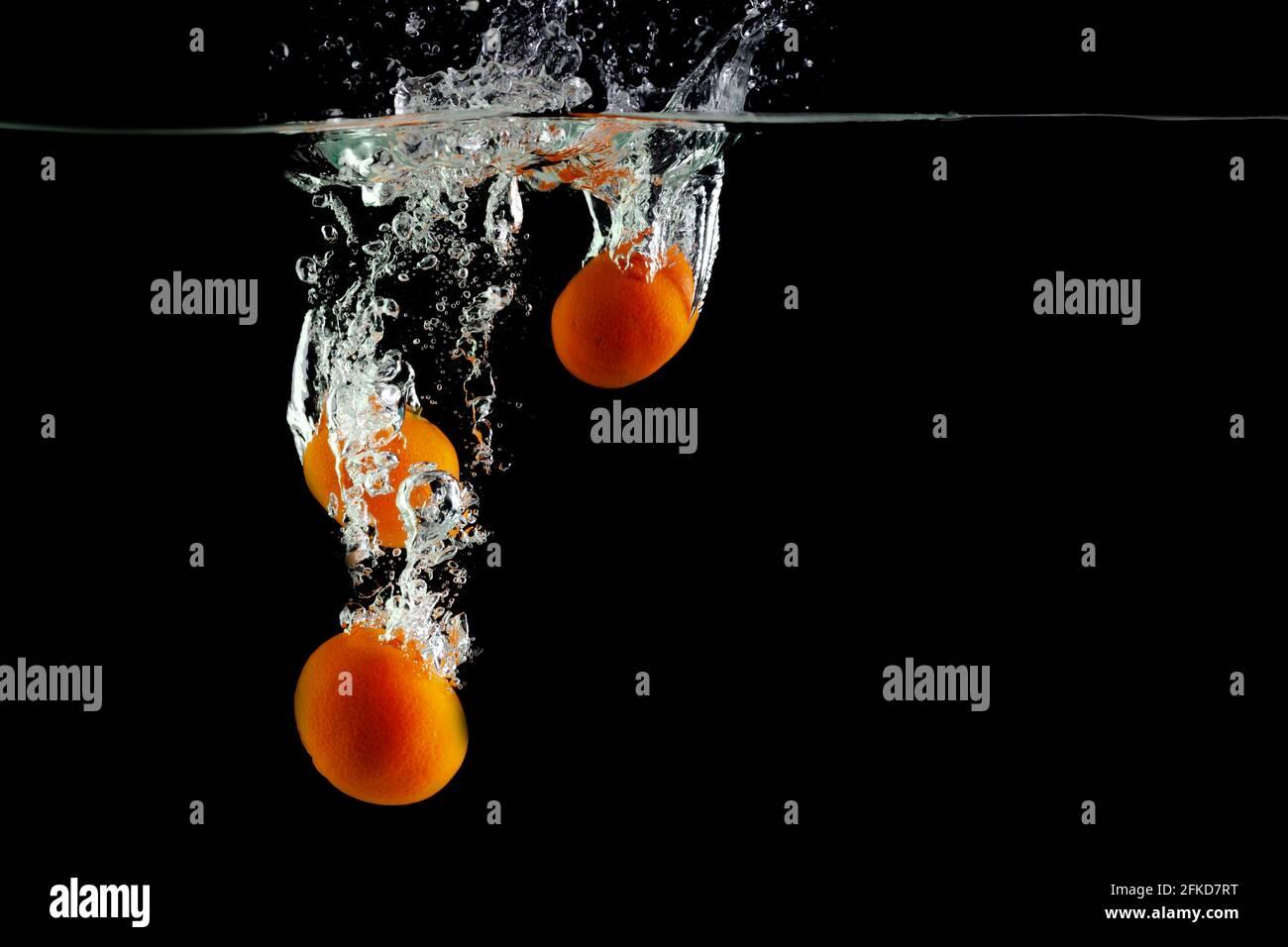 Drei Mandarinen fallen auf schwarzem Grund ins Wasser Stockfoto