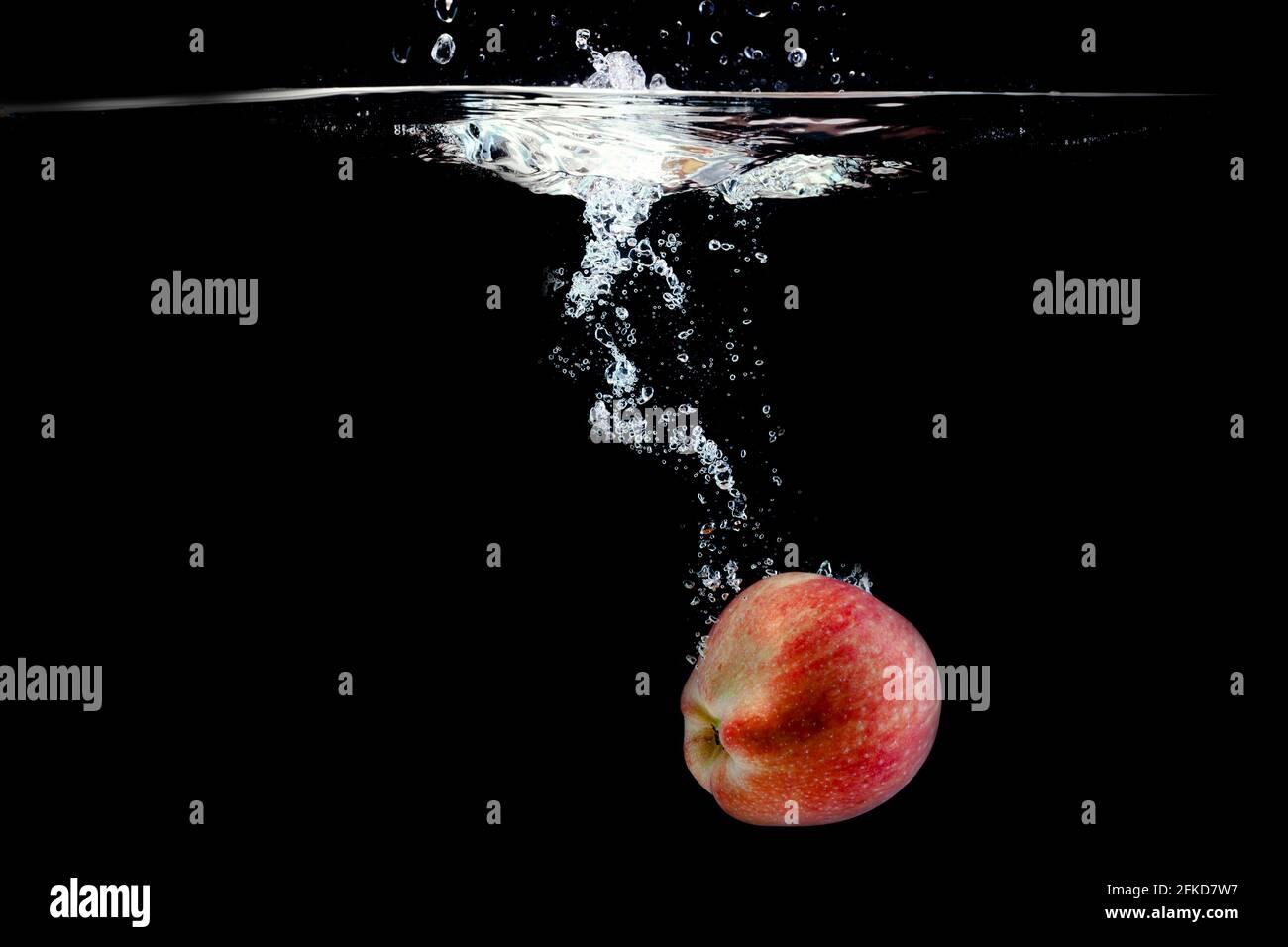 Reifer roter Apfel fiel mit Spritzern ins Wasser Stockfoto