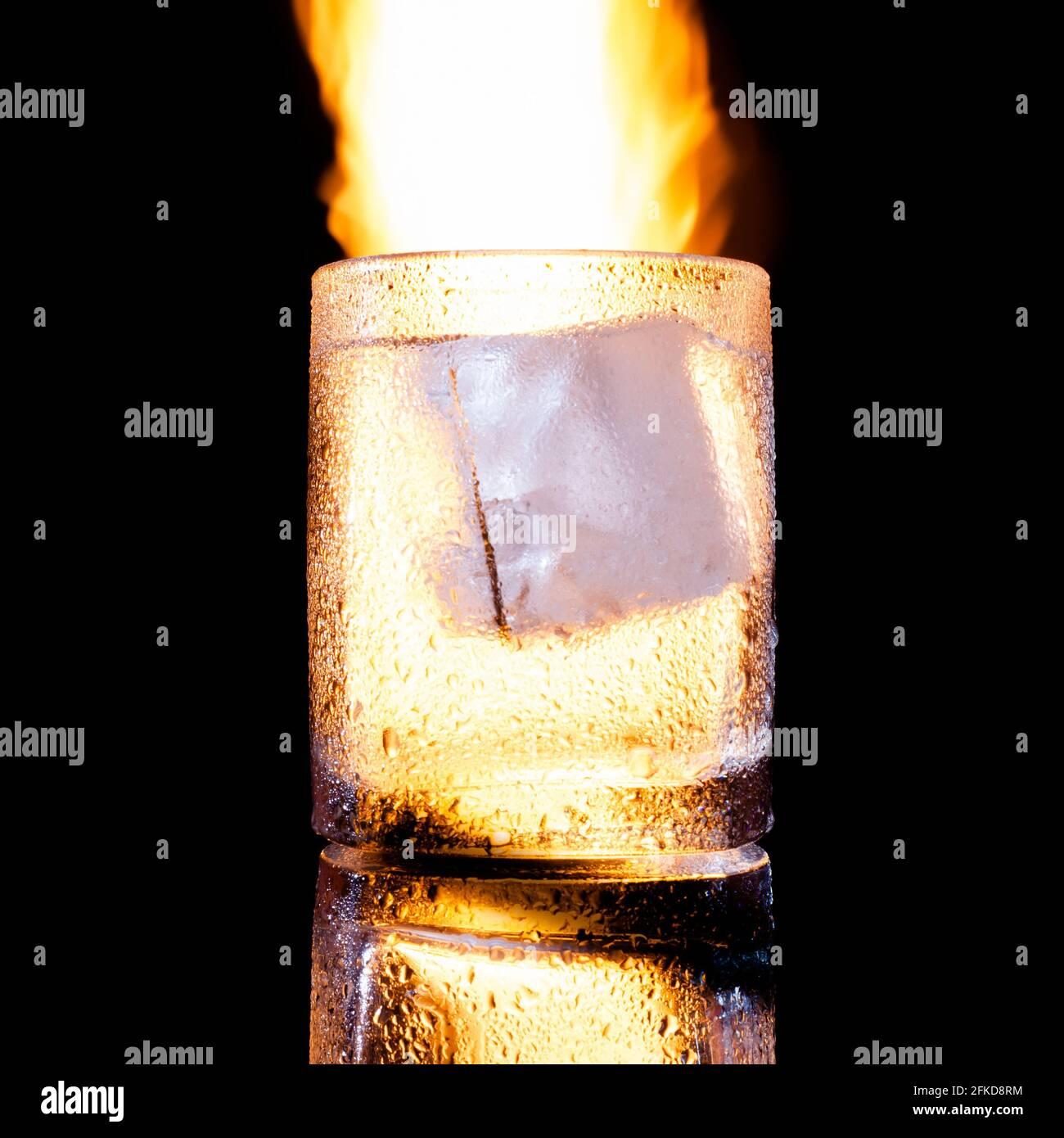 Glas mit einem Stück Eis vor dem Hintergrund von Feuer Stockfoto
