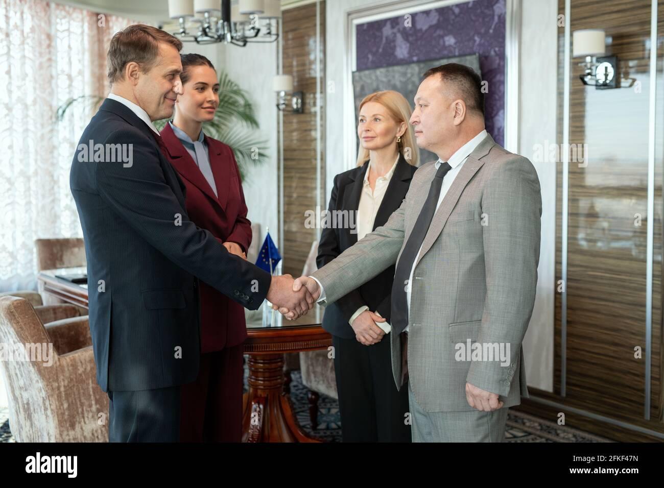Eine Gruppe erfolgreicher eleganter Geschäftsleute, die sich im Sitzungssaal die Hände schütteln Stockfoto