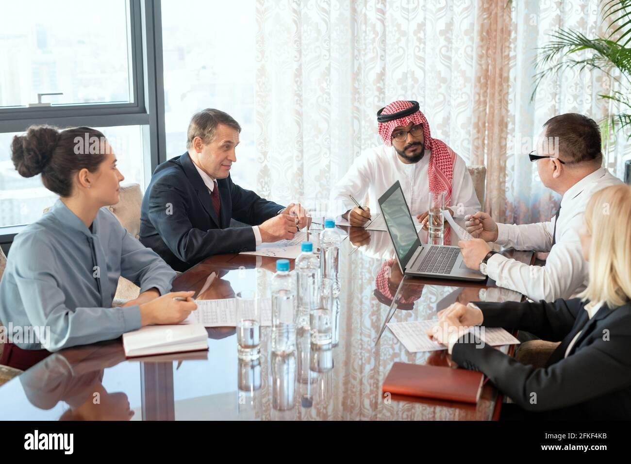 Eine Gruppe von Delegierten oder Geschäftsleuten, die an einem Tisch sitzen Während des Meetings Stockfoto
