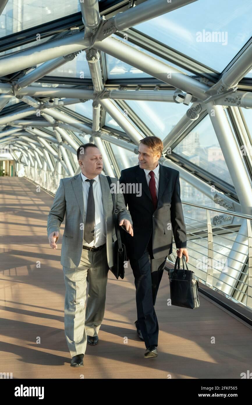 Männer in Anzügen, die im modernen Gebäude und durch den Gang laufen Sprechen Stockfoto