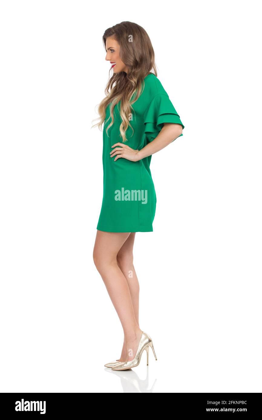 Junge Frau im grünen Minikleid und goldenen High Heels steht mit den Händen auf der Hüfte. Seitenansicht. Studioaufnahme in voller Länge, isoliert auf Weiß. Stockfoto