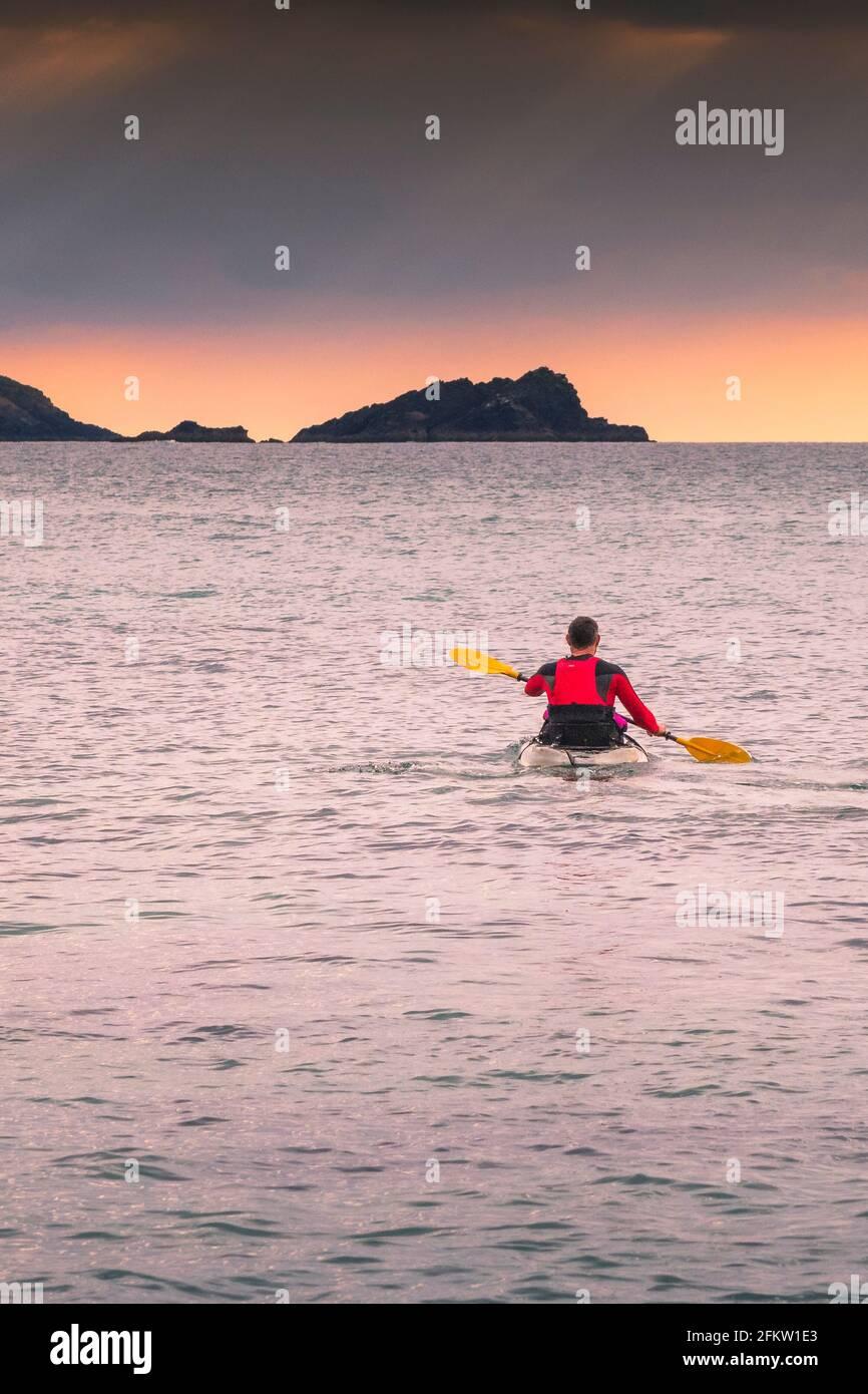 Ein Kajakfahrer paddelt auf dem Meer in der Fistral Bay in Newquay in Cornwall. Stockfoto