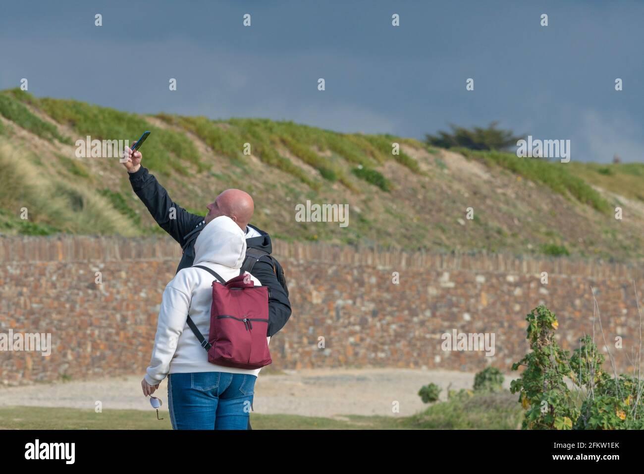 Ein paar Urlauber, die ein Smartphone benutzen, um ein Selfie-Foto im Urlaub in Newquay in Cornwall zu machen. Stockfoto