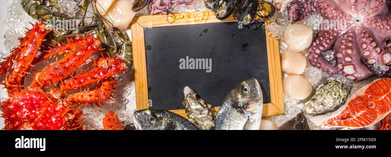Set aus verschiedenen frischen rohen Meeresfrüchten - Kraken, Krabben, Tintenfisch, Garnelen Garnelen, Auster, Miesmuscheln, Lachs Thunfisch dorada Fisch mit Gewürzen von Kräutern Zitrone, weißer Rücken Stockfoto