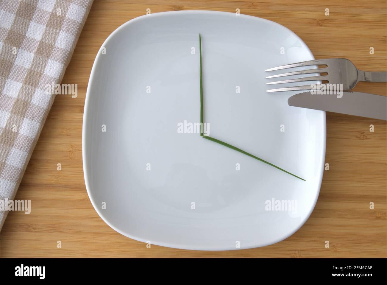 Draufsicht auf eine weiße Platte mit einem Drittel markiert Für intermittierendes Fasten Stockfoto