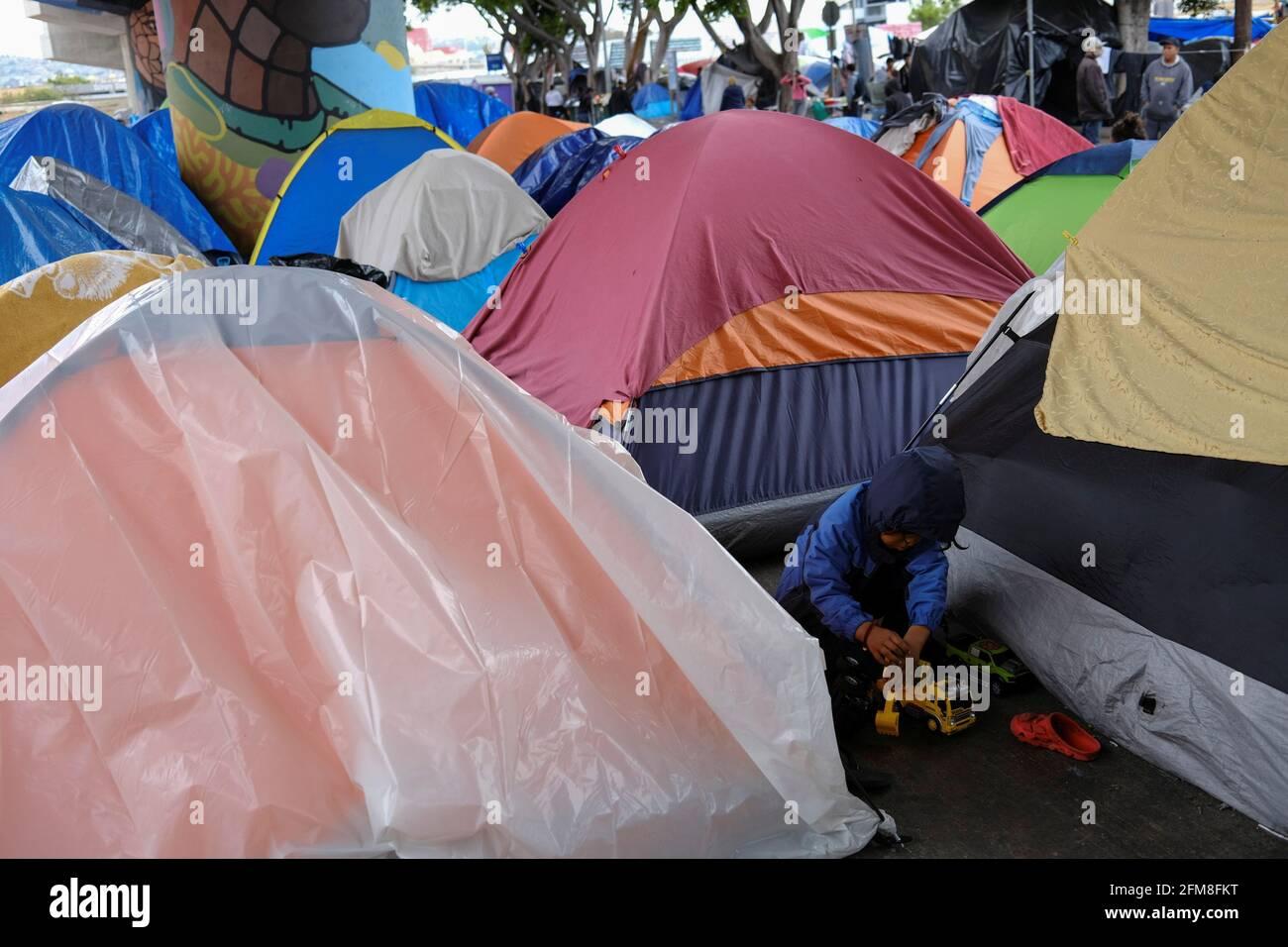 Ein Migrantenkind spielt mit Spielzeugautos in einem provisorischen Lager am Grenzhafen von El Chaparral, der in die USA einführt, in Tijuana, Mexiko, am 23. April 2021. Bild aufgenommen am 23. April 2021. REUTERS/Toya Sarno Jordan Stockfoto