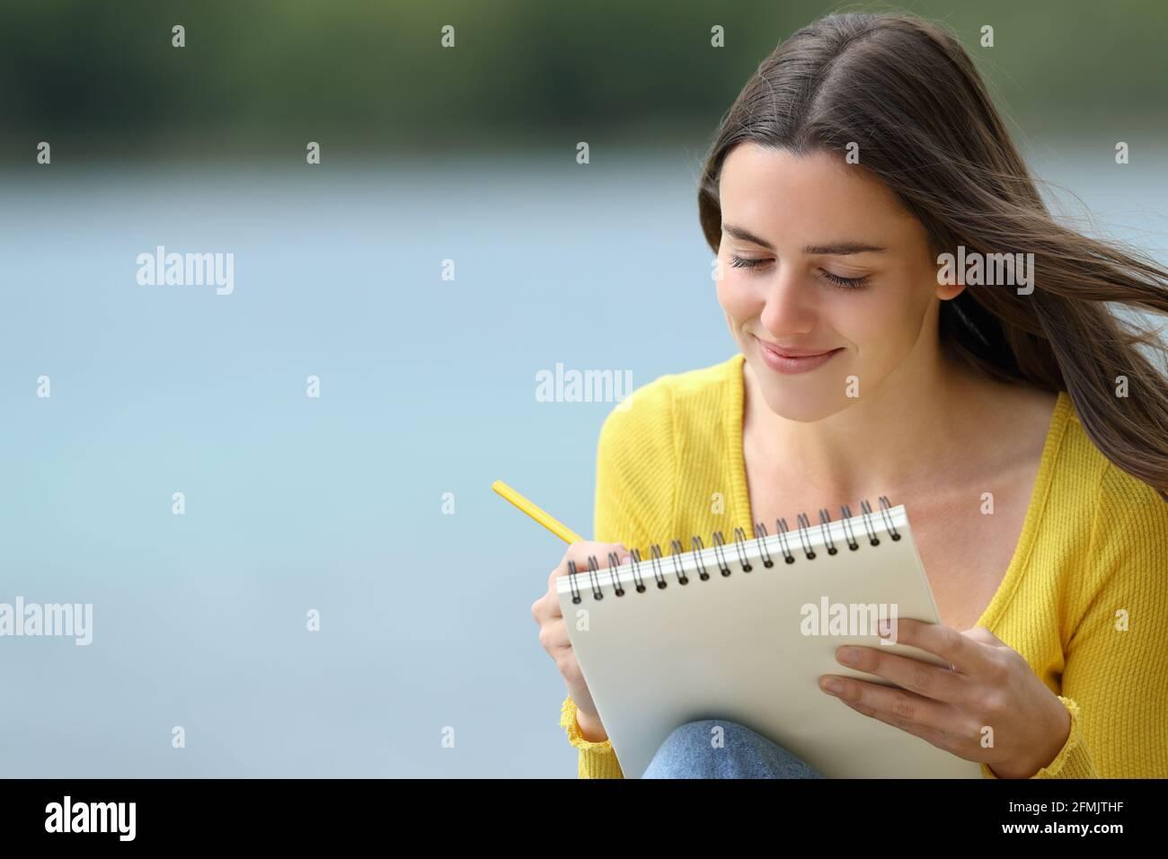 Glückliche Frau, die in einem Notizbuch neben einem See sitzt Stockfoto