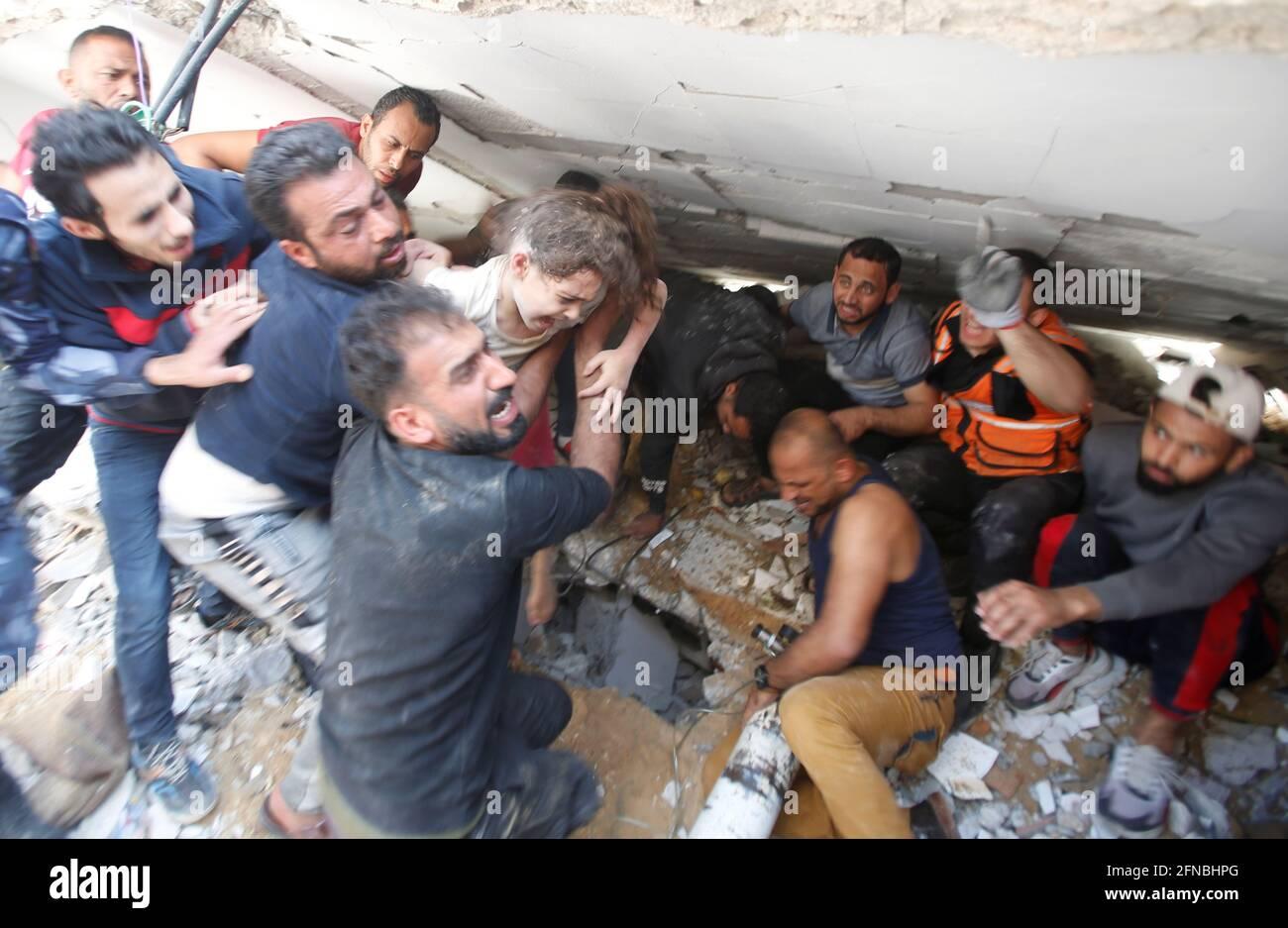 Rettungskräfte tragen ein Mädchen, während sie am 16. Mai 2021 in Gaza-Stadt in Trümmern am Ort der israelischen Luftangriffe nach Opfern suchen. REUTERS/Mohammed Salem Stockfoto
