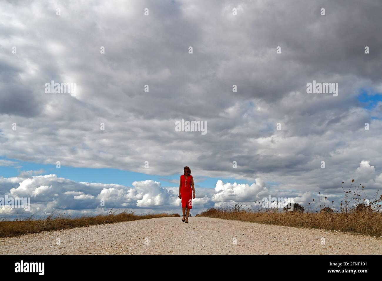 Frau, die allein auf der geraden Landstraße läuft. Wolkiger Himmel. Frankreich. Stockfoto