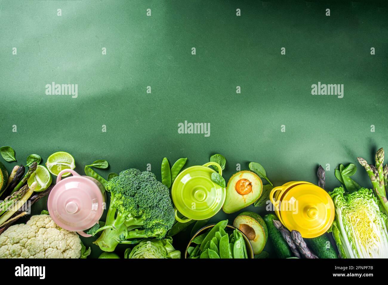 Verschiedene Bio-grüne Frühlingsgemüse-Zutaten mit leeren bunt portionierten Kochtöpfen auf dunkelgrünem Küchentisch, Draufsicht. Diät gesunde Suppe Stockfoto