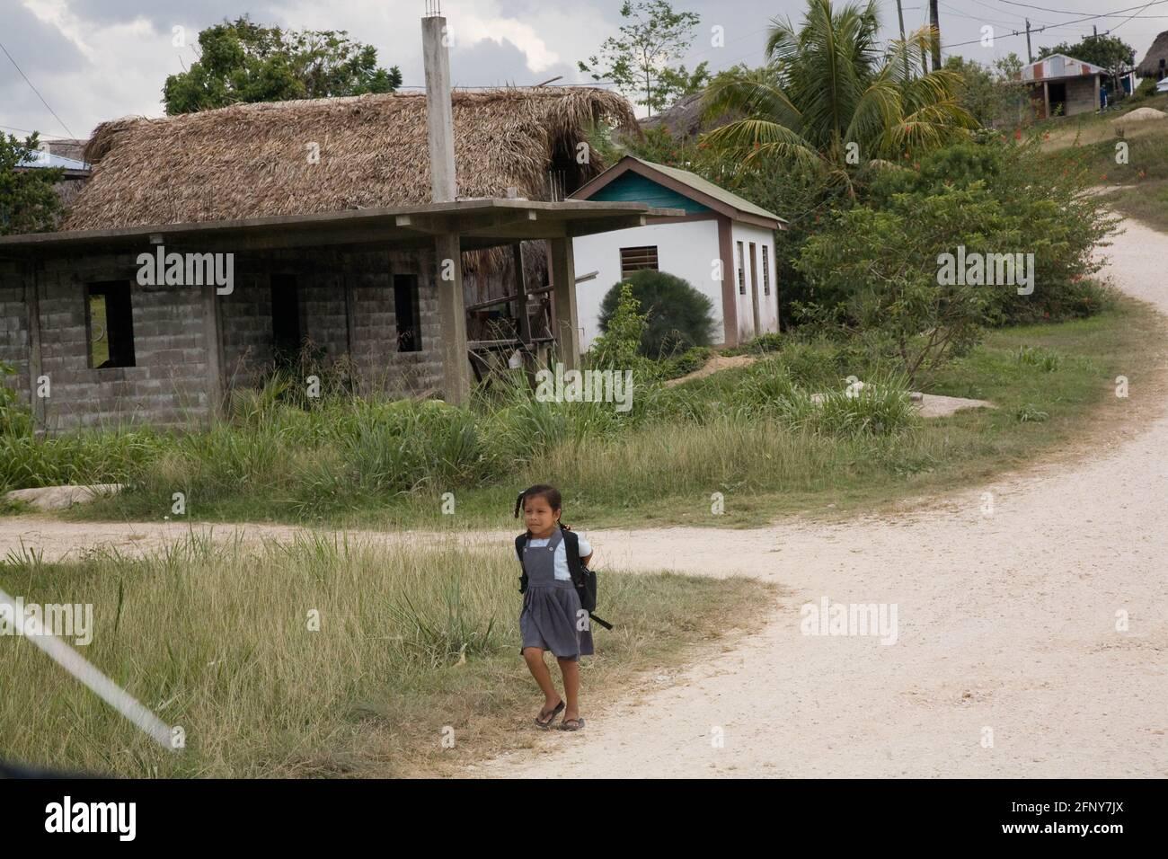 Ein junges Mädchen, das von der Schule in der Maya-Gemeinde San Miguel, Toledo, Belize, nach Hause geht Stockfoto