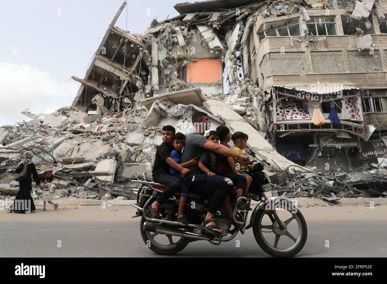 Palästinenser fahren mit dem Motorrad am Ort eines israelischen Luftanschlags vorbei, nach dem Waffenstillstand der Hamas in Gaza am 21. Mai 2021. REUTERS/Suhaib Salem Stockfoto