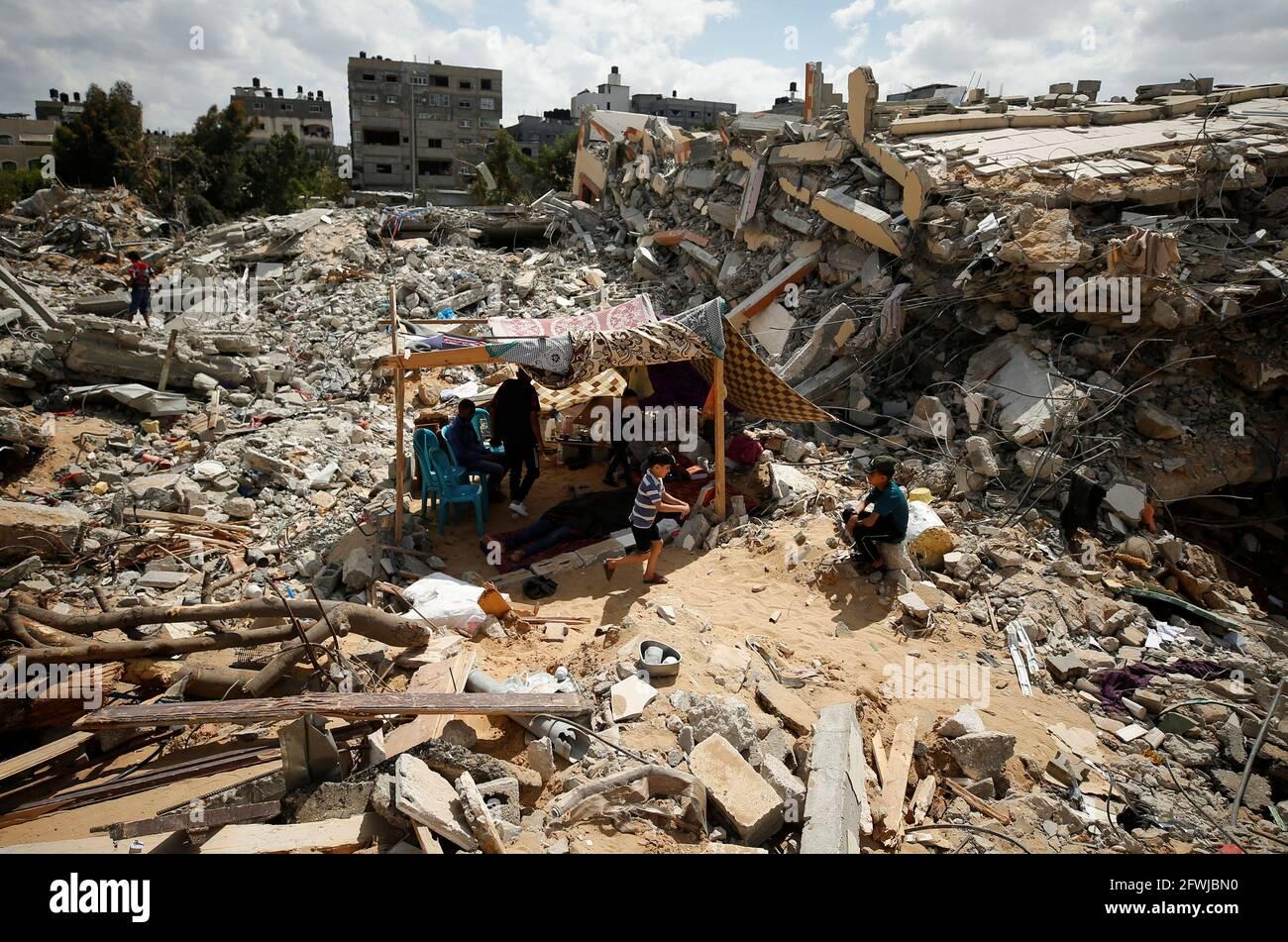 Palästinenser sitzen in einem provisorischen Zelt inmitten der Trümmer ihrer Häuser, die durch israelische Luftangriffe während der Kämpfe zwischen Israel und der Hamas im Gazastreifen am 23. Mai 2021 zerstört wurden. REUTERS/Mohammed Salem Stockfoto
