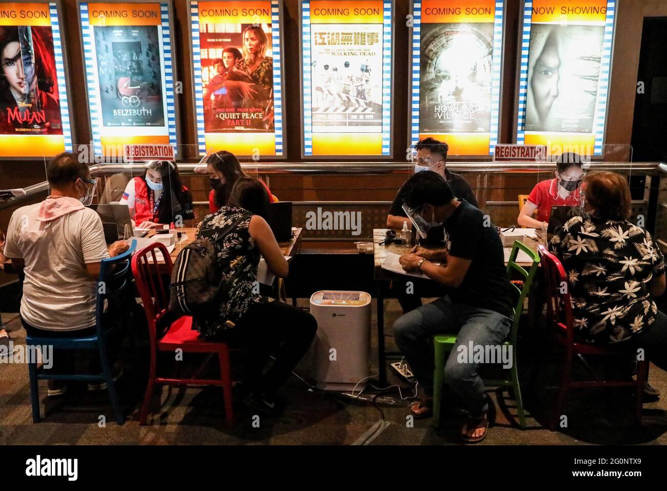 Menschen mit Schutzmasken und Gesichtsschilden registrieren sich, bevor sie ihre Dosis der Sinovac COVID-19-Impfung in einem Kino erhalten, das in San Juan City, Metro Manila, Philippinen, zu einer Impfstelle wurde. Stockfoto