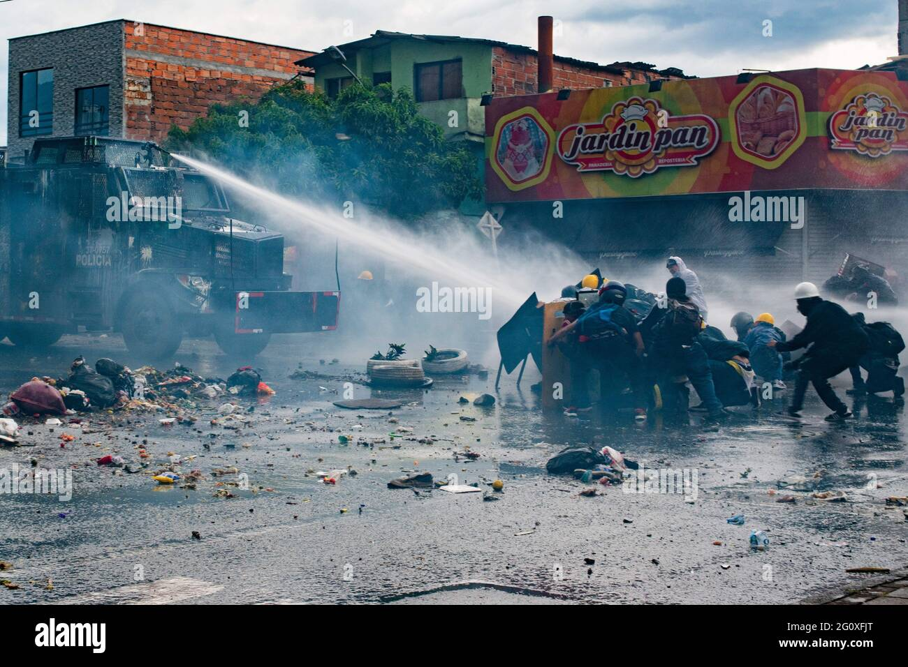 2. Juni 2021, Medellin, Antioquia, Kolumbien: Demonstranten hüten sich hinter handgefertigten Schilden, als ein bewaffnet LKW während der Zusammenstöße mit der kolumbianischen Bereitschaftspolizei (ESMAD) Wasser auf sie schießt, während regierungsfeindliche Proteste in eine 5. Woche gegen die Gesundheits- und Steuerreform von Präsident Ivan Duque ansteigen, Und Polizeimissbrauch von Behördenfällen in Medellin, Kolumbien, am 2. Juni 2021. (Bild: © Miyer Juana/LongVisual über ZUMA Wire) Stockfoto