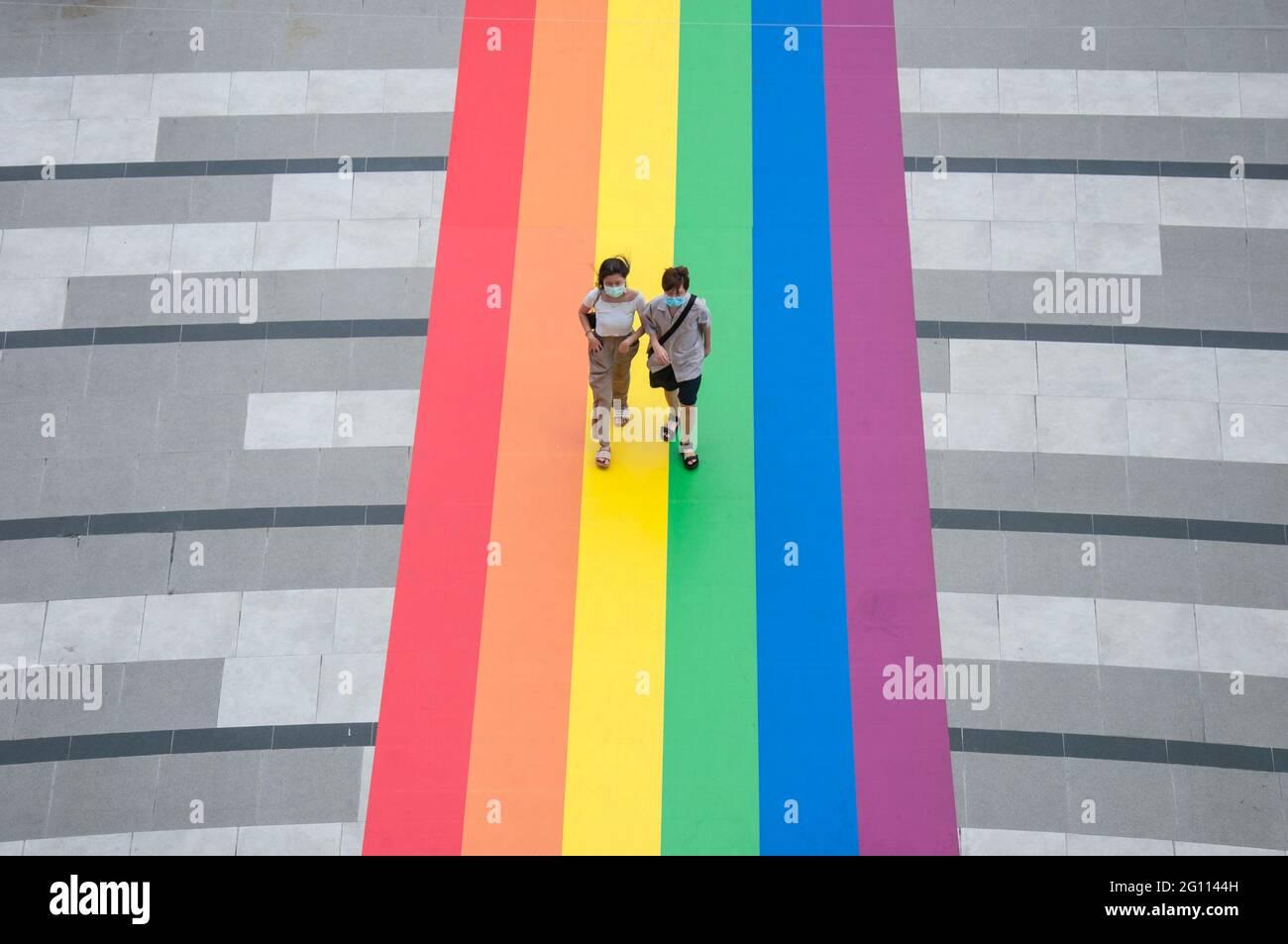 """Bangkok, Thailand. Juni 2021. Die Menschen laufen auf einer riesigen Regenbogenfahne, die am Eingang des Einkaufszentrums Samyan Mitrtown angebracht ist.Samyan Mitrtown, ein gemischtes Einkaufszentrum, ein Büro, Die Wohn- und Freizeitentwicklung feierte den LGBTQ Pride Month 2021, indem sie den Boden am Eingang und den Tunnel der Mall mit der riesigen und langen Regenbogenfahne dekorierte. """"Samyan Mitr Proud 100% Love"""" in Bangkok, Thailand. Kredit: SOPA Images Limited/Alamy Live Nachrichten Stockfoto"""