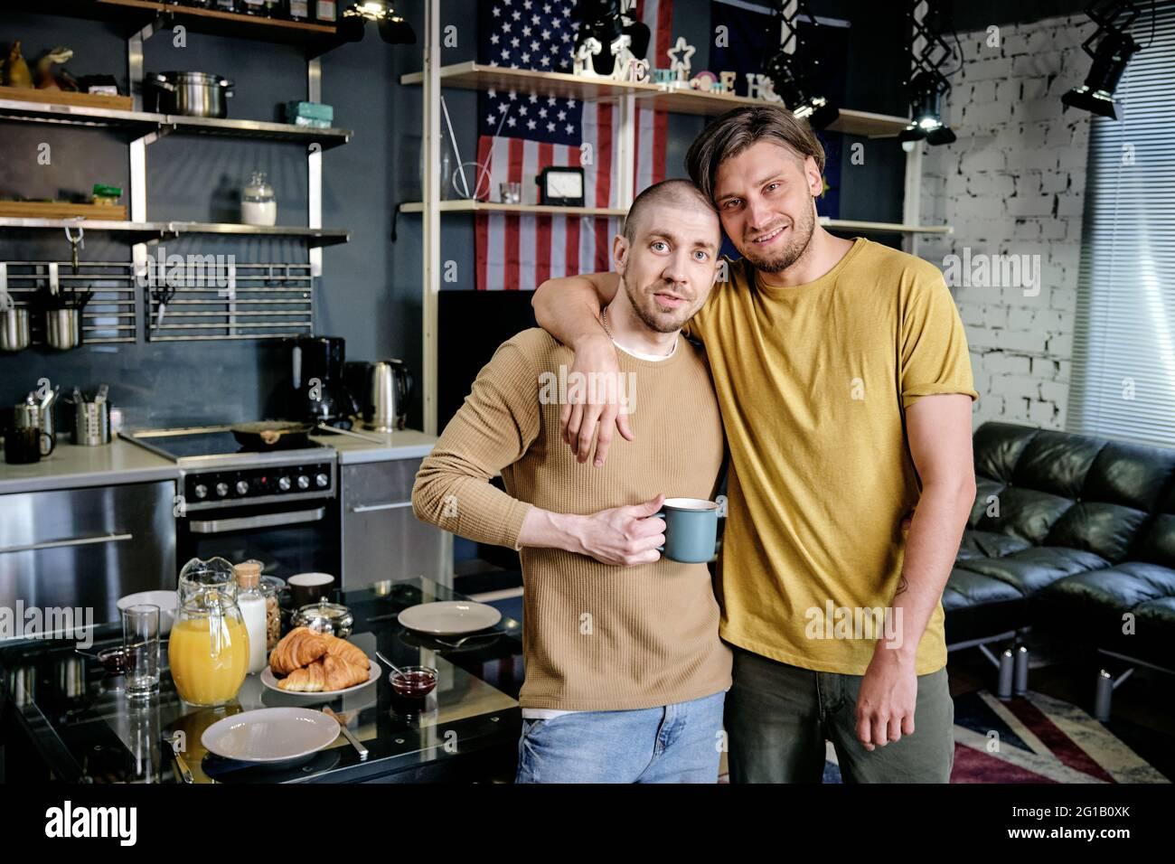 Lächelnder, schwuler Mann umarmt seinen Mann vor der Kamera Stockfoto