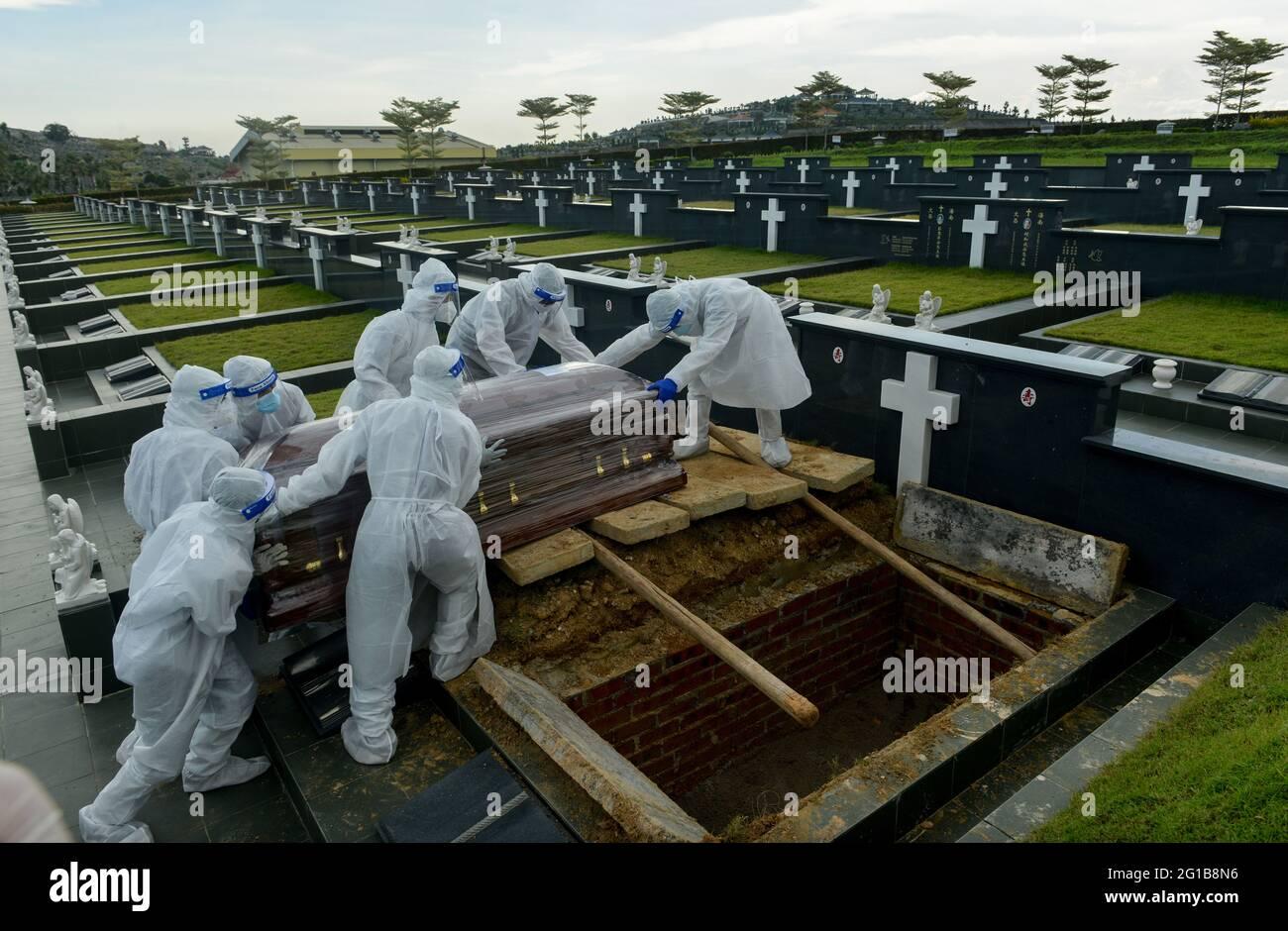 Klang, Selangor, Malaysia. Juni 2021. Mitarbeiter des Bestattungsdienstes, die persönliche Schutzausrüstung tragen, bereiten sich darauf vor, den Sarg eines Opfers der Coronavirus-Krankheit (COVID-19) auf dem Friedhof zu begraben. Kredit: Keepy/ZUMA Wire/Alamy Live Nachrichten Stockfoto