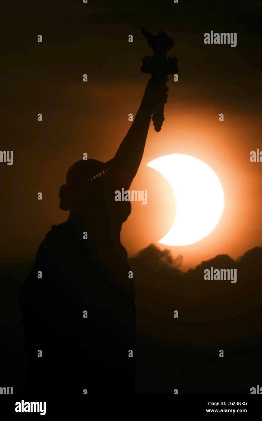 Die teilweise verfinsterte Sonne geht Anfang des 10. Juni 2021 hinter der Freiheitsstatue in New York City, New York, USA, auf. REUTERS/Bjoern Kils/New York Media Boat Stockfoto