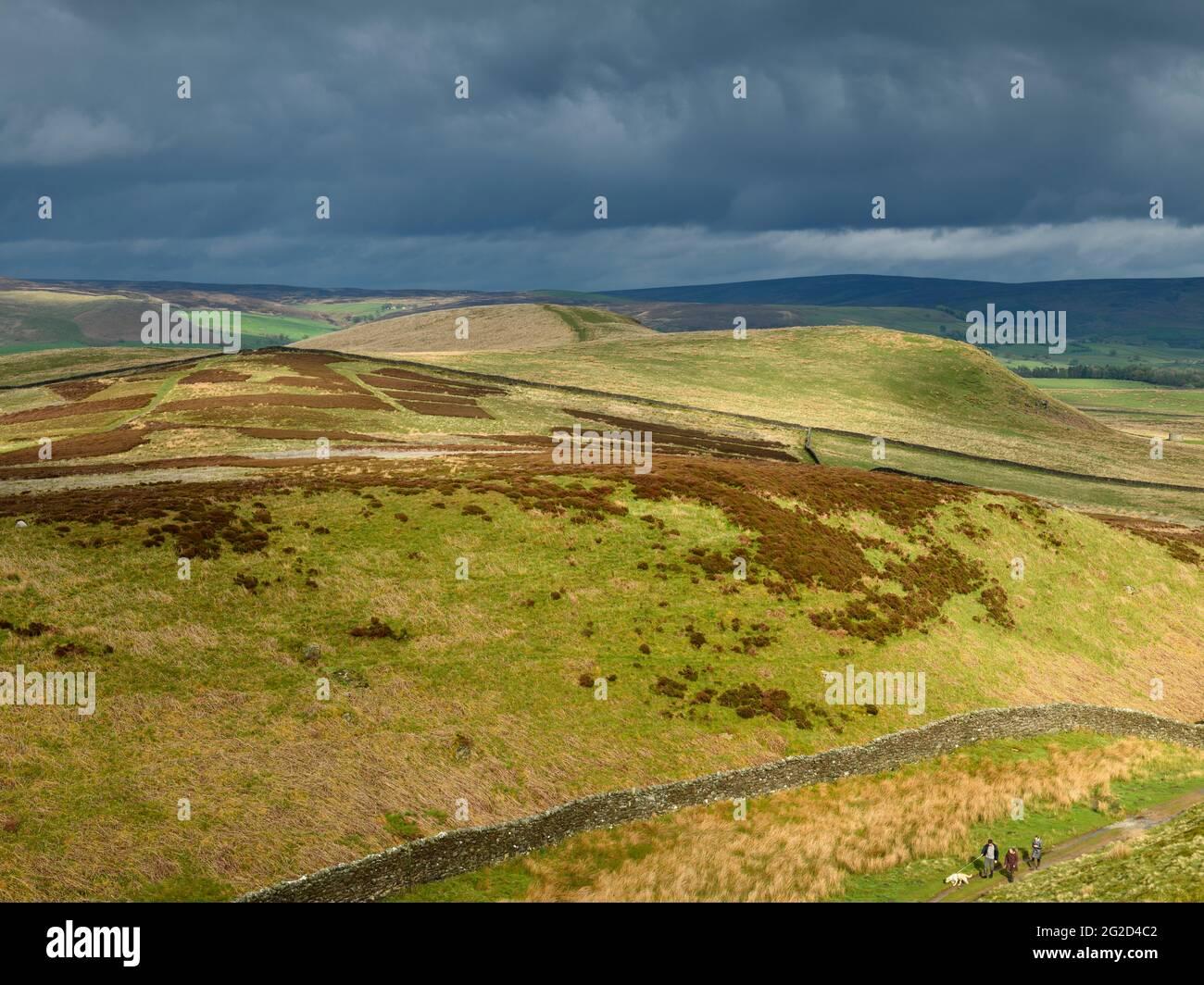 Malerische ländliche Landschaft & dunkle Regenwolken (hügelige Gegend, sanft geschwungene, sonnenbeschienenen Hügel, Menschen, die mit dem Hund spazieren) - Blick auf Wharfedale, Yorkshire Dales England, Großbritannien Stockfoto