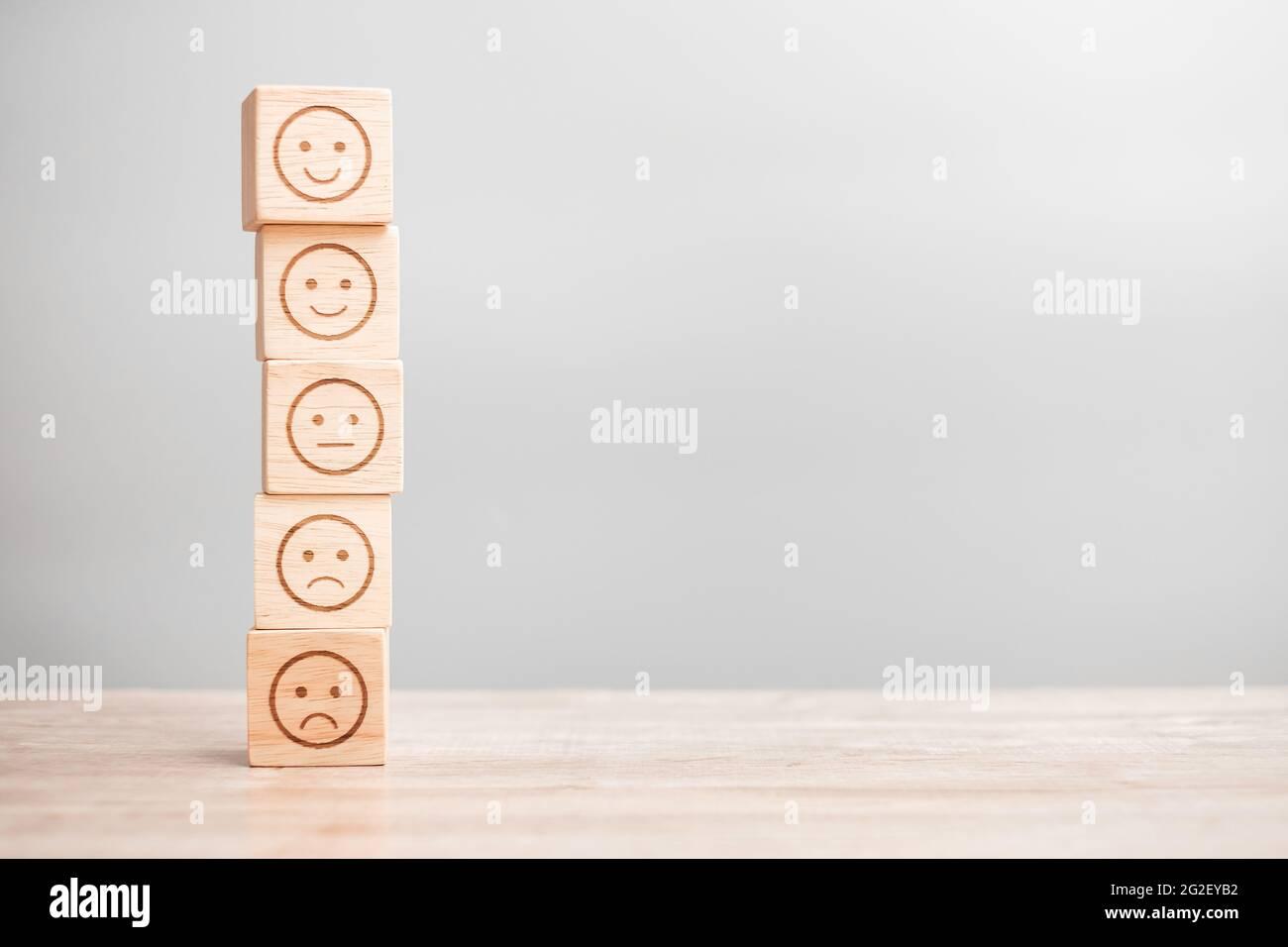 Emotionsgesicht-Symbol auf Holzblöcken. Service Rating, Ranking, Customer Review, Zufriedenheit, Bewertung und Feedback-Konzept Stockfoto