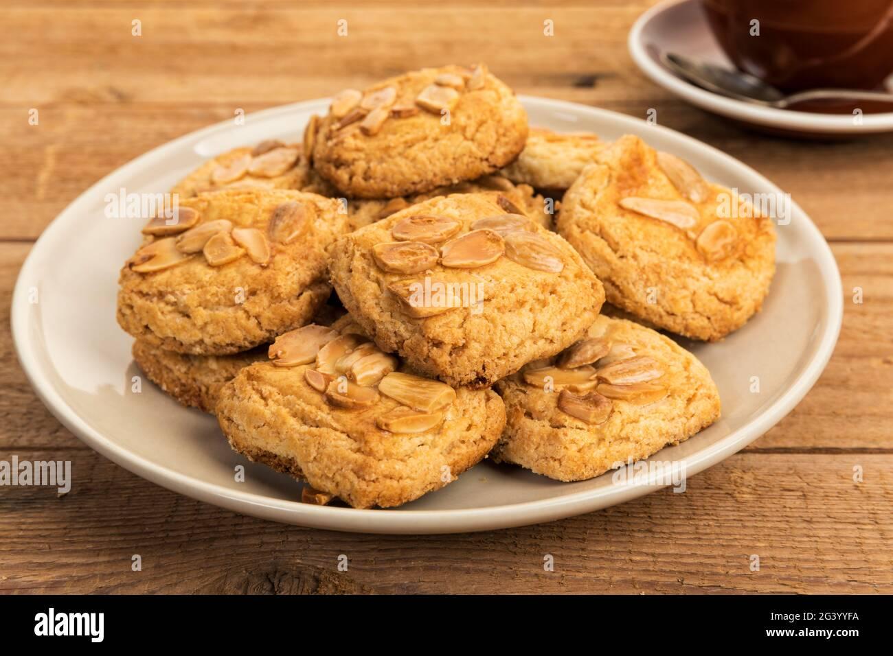 Spanische Almendrados Kekse mit Mandeln auf einem Teller, auf einem rustikalen Couchtisch Stockfoto