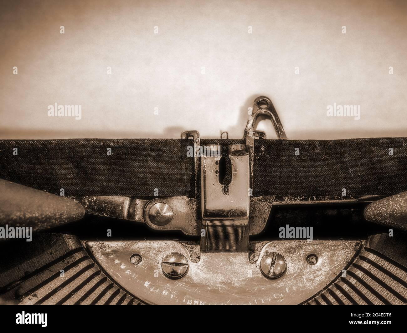 Nahaufnahme der Schreibmaschine mit einem leeren Blatt Papier, das ...