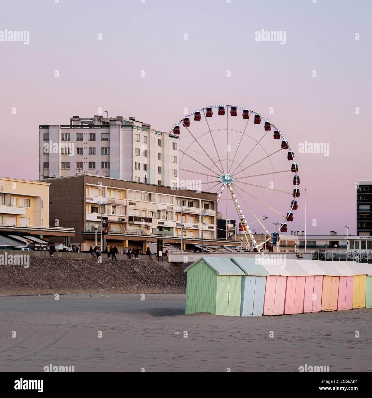 Pastellfarbene Strandhütten und Riesenrad am Strand Von Berck in Frankreich Stockfoto