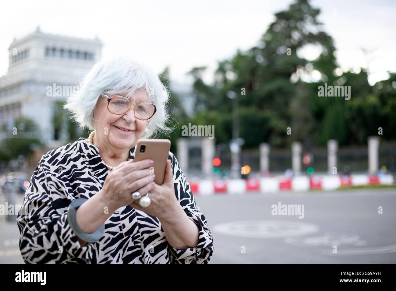 Ältere Frau, die auf der Straße mit dem Handy telefoniert