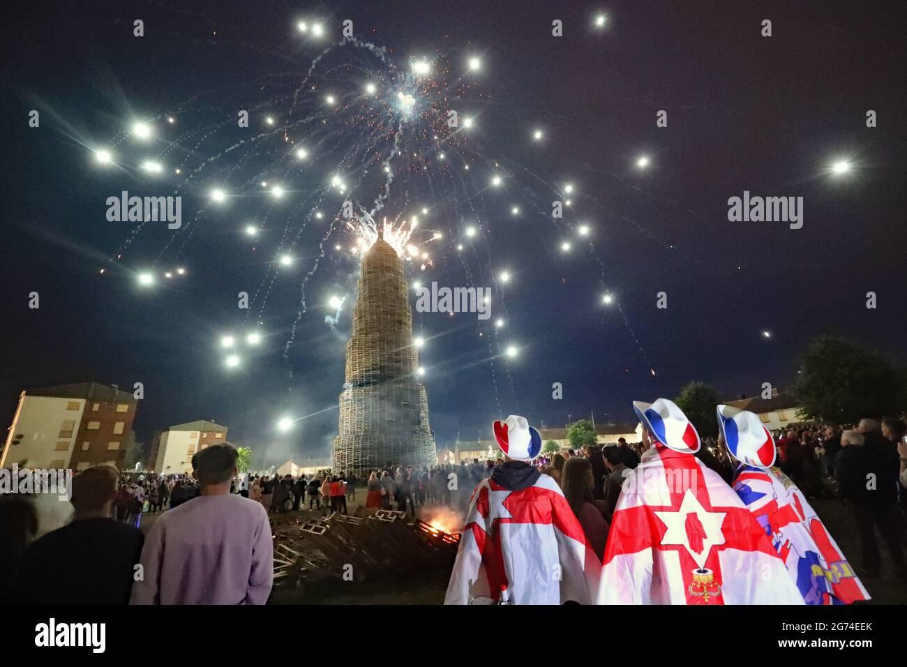 Menschenmengen beobachten ein Feuerwerk, bevor das riesige Lagerfeuer in der loyalistischen Corcrain-Gegend von Portadown, Co Armagh, in der elften Nacht angezündet wird, um die zwölften gedenkfeiern einzuläuten. Bilddatum: Samstag, 10. Juli 2021. Stockfoto