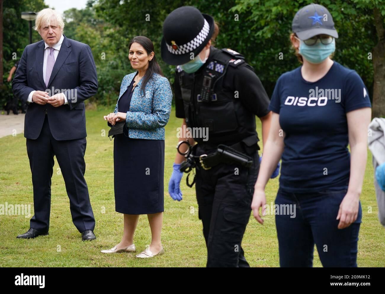 Premierminister Boris Johnson und Innenminister Priti Patel beobachten bei einem Besuch des Polizeihauptquartiers von Surrey in Guildford, Surrey, anlässlich der Veröffentlichung des Plans zur Bekämpfung von Verbrechen durch die Regierung eine Durchsuchung. Bilddatum: Dienstag, 27. Juli 2021. Stockfoto