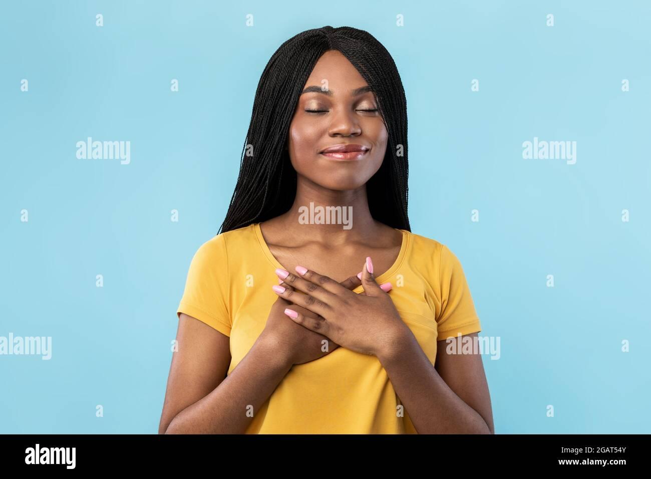Freundlichkeit Und Dankbarkeit. Dankbare Afroamerikanische Frau Drückt Die Hände An Die Brust Und Posiert Lächelnd Mit Geschlossenen Augen Auf Blauem Hintergrund. Studio Portrait Stockfoto