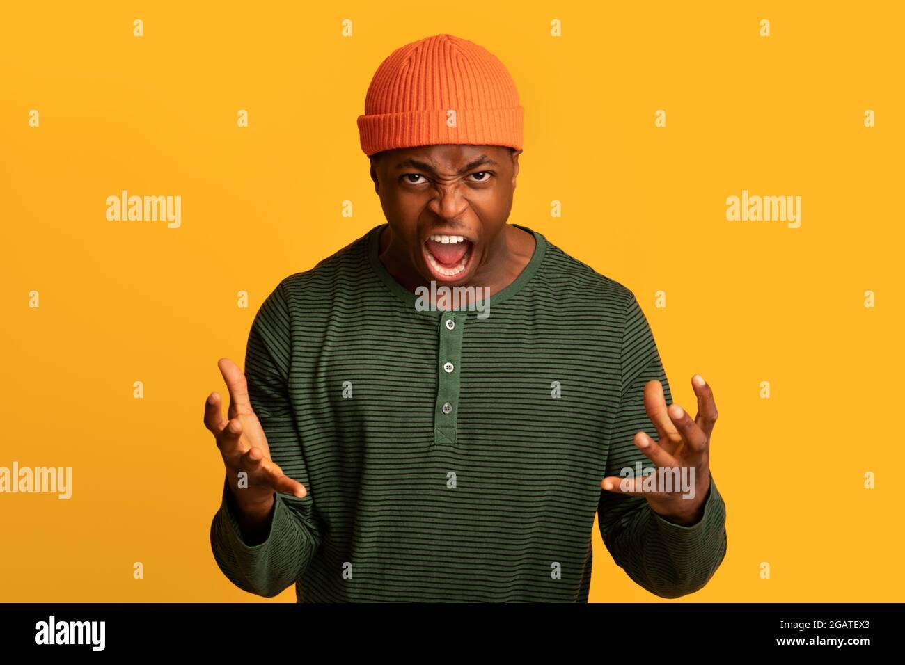 Porträt eines wütenden afroamerikanischen Mannes, der vor Wut vor die Kamera schrie, eines sehr wütenden schwarzen Mannes, der die Hände hob und wütend schrie, während er isola stand Stockfoto