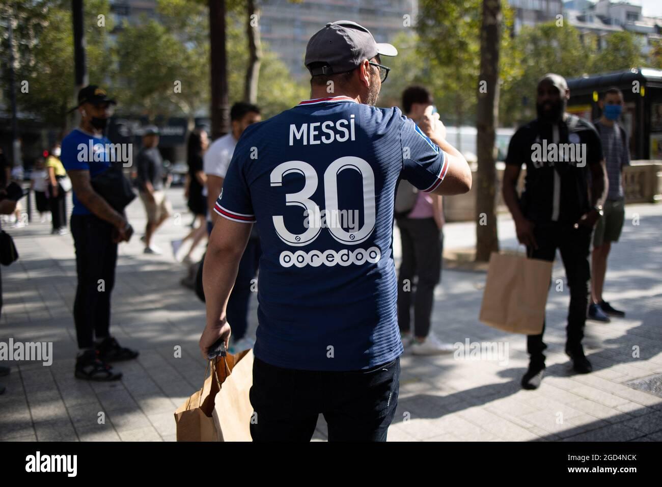 Paris, Frankreich. August 2021. Ein Unterstützer trägt ein Trikot des argentinischen PSG-Fußballspielers Lionel Messi, das er am 11. August 2021 im Laden des Fußballclubs Paris-Saint-Germain (PSG) auf der Champs Elysees in Paris gekauft hat. Messi unterzeichnete am 10. August 2021 einen zweijährigen Vertrag mit PSG mit der Option eines zusätzlichen Jahres. Der 34-Jährige wird in Paris die Nummer 30 tragen, die er zu Beginn seiner beruflichen Laufbahn bei Barca hatte. Foto von Raphael Lafargue/ABACAPRESS.COM Quelle: Abaca Press/Alamy Live News Stockfoto