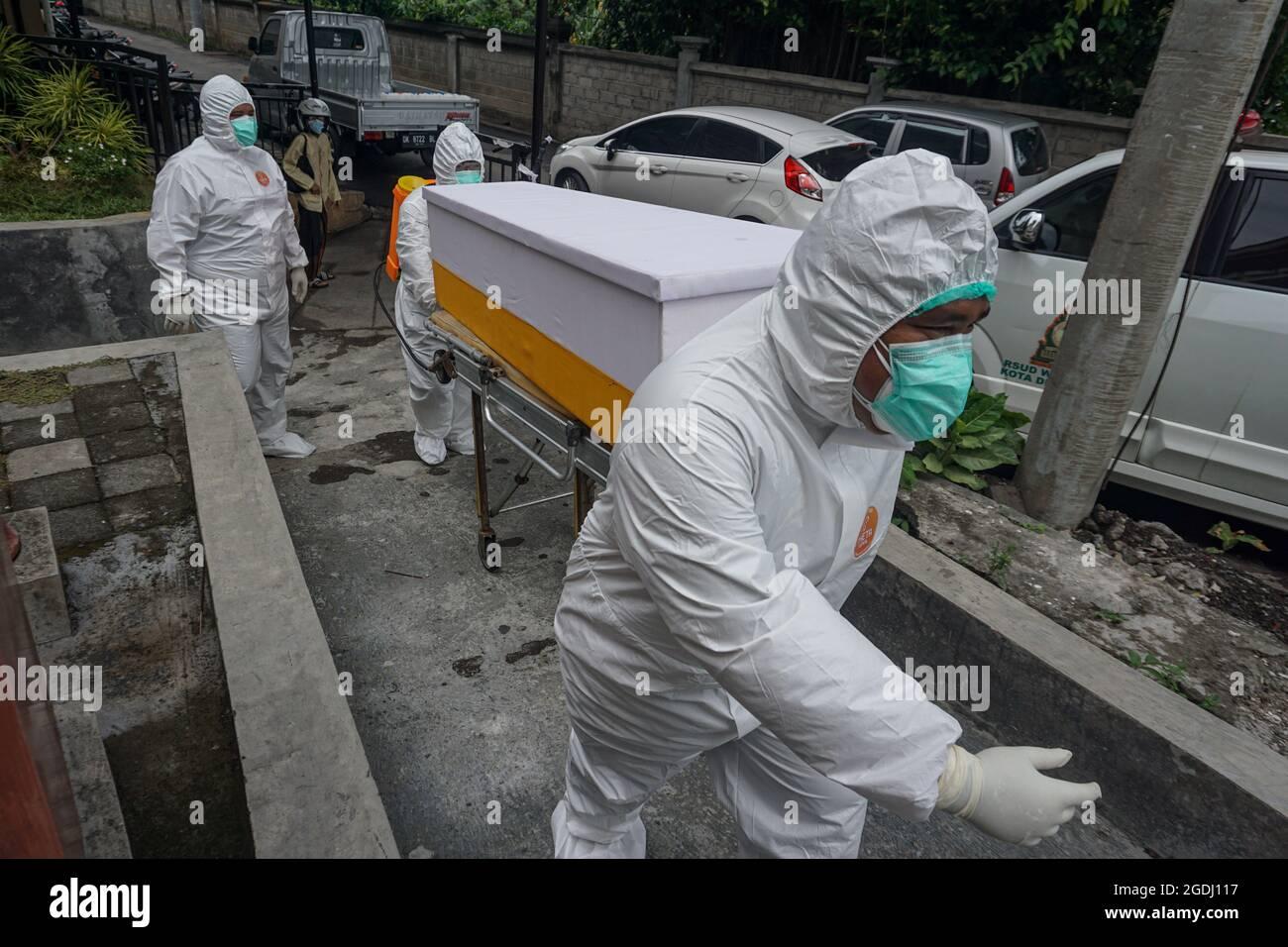 """Denpasar, Bali, Indonesien. August 2021. Arbeiter werden das tote Opfer aus dem Isolationsraum holen. Die Leichenhalle des Wgaya Krankenhauses ist überlastet, da die Zahl der Toten von Covid-19 deutlich zunimmt. Die balinesische Hindu-Tradition wartet darauf, dass der ausgewählte """"gute Tag"""" für die toten Opfer eingeäschert wird. Wie am Donnerstag, dem 12. August, hat die Provinz Bali in 24 Stunden 1.353 neue Fälle und 35 Tote zu vermehren. (Bild: © Dicky BisinglasiZUMA Press Wire) Stockfoto"""