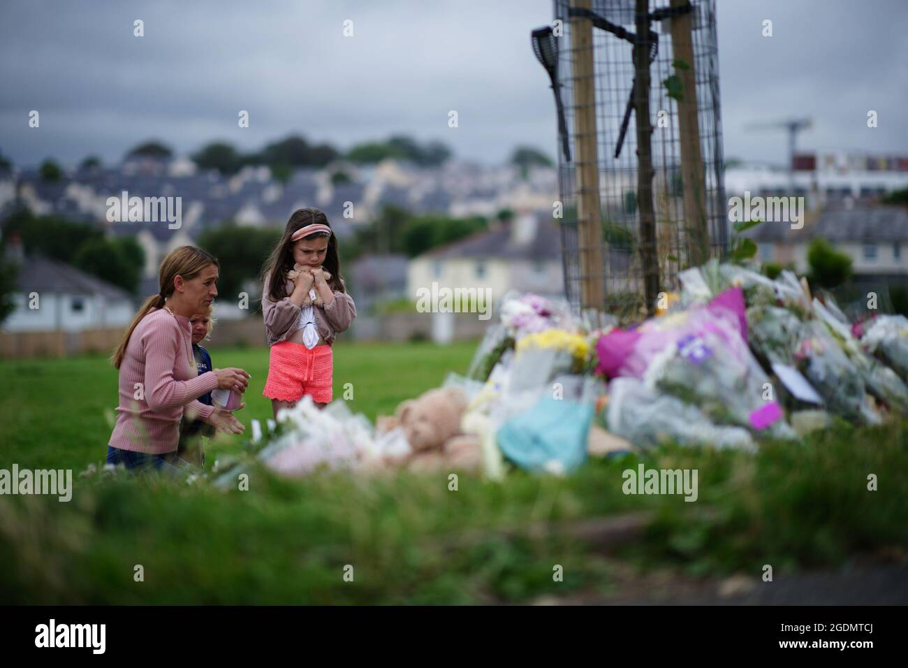 Eine Frau und zwei junge Mädchen betrachten Blumengebete in Plymouth, bei denen sechs Personen, darunter der Täter, bei einem Schusswaffenereignis am Donnerstagabend an Schussverletzungen starben. Bilddatum: Samstag, 14. August 2021. Stockfoto